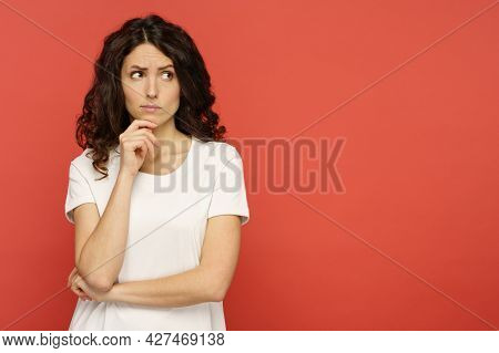 Doubtful Young Woman Touching Her Chin, Skeptic And Pensive Think With Folded Arms Looking Up To Cop