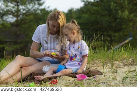 Mother With Baby Playing With Sand On The Beach, Sculpting Easter Cakes. The Girl Is 4 Years Old. Ch