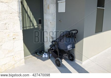 Close Up View Of Baby Carriage Outside Infront Of Grey Door. Greece.