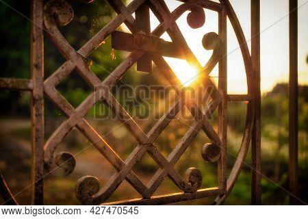 A Golden Metal Gate Door In The Back-lit Sunlight