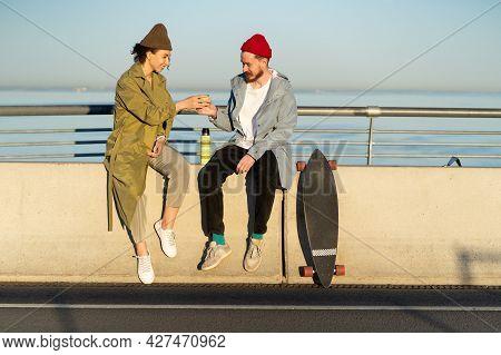 Happy Couple Drinking Hot Tea Outdoors Sitting On Bridge Broadwalk Dressed In Trendy Street Fashion