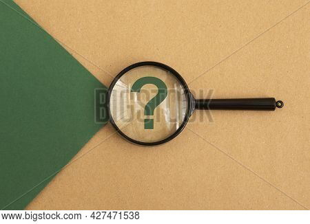 Question Mark Through Magnifying Glass On Green And Brown Background, Top View. Concept Of Ecology Q