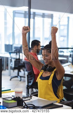 Mixed race female creative sitting at desk celebrating raising her arms and smiling. modern office of a creative design business.