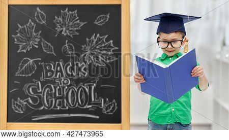 education, learning and people concept - happy little student boy in bachelor hat or mortarboard and eyeglasses over chalkboard with back to school lettering on background