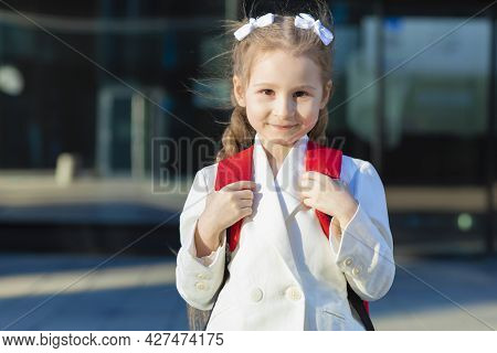 Beautiful Kid Back To School. Happy Cute Confident Girl In Uniform. Schoolchild In White Suit With R