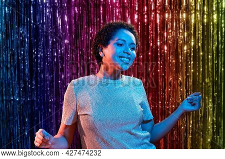 leisure, clubbing and nightlife concept - smiling young african american woman dancing in ultraviolet neon lights at party over rainbow foil curtain background