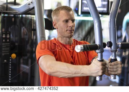 Attractive Strong Handsome Young Man Pumping Up Muscles In Gym. Muscle Athlete Guy Workout. Exercise