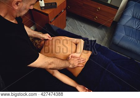 High Angle View Of Professional Chiropractor, Osteopath, Masseur Doing Remedial Therapeutic Body Mas