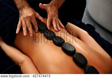 Close-up Of Masseur Laying Hot Stones Along Spine Of Young Woman And Doing Ayurvedic Hot Stone Massa