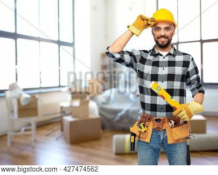 repair, construction and building concept - happy smiling male worker or builder in helmet with level over home room background
