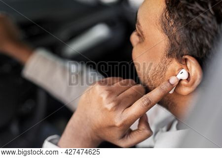 transport, people and technology concept - close up of indian man or driver with wireless earphones or hands free device driving car