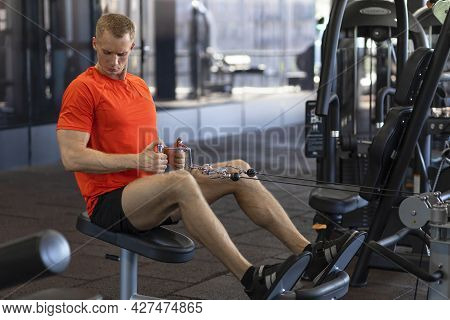 Attractive Strong Handsome Athlete Man Pumping Up Muscles In Gym. Muscle Guy Workout. Exercises For