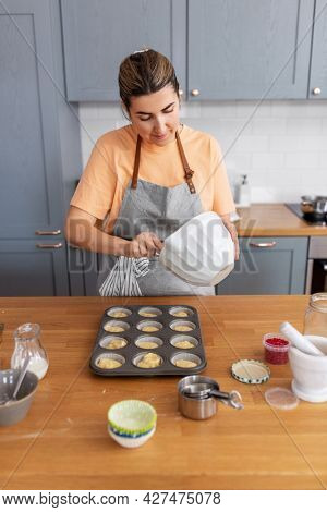 culinary, bake and people concept - happy smiling young woman cooking food on kitchen at home putting batter in baking dish for cupcakes