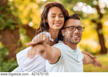 leisure, vacation and people concept - happy couple having fun at summer park