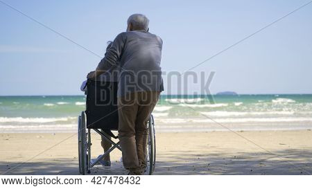 Happy Asian Back Elderly Woman Disabled Sitting In Wheelchair And Husband Is A Wheelchair User On Th