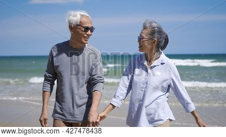 Happy Asian Senior Man And Woman Couple Holding Hands Walking From The Beach Sunny With Bright Blue