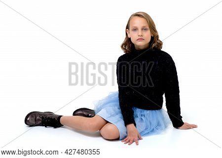 Beautiful Girl In Black Jumper And Light Blue Fluffy Skirt Sitting On Her Knees On Floor. Pretty Blo