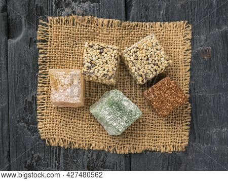 Top View Of The Pieces Of Turkish Delight On A Piece Of Burlap On A Wooden Table. Oriental Sweets.