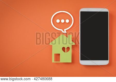 White Mobile Phone With Clipping Path On Touchscreen, Green House Paper  And Chat Icon On Vivid Oran