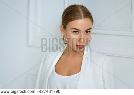 Portrait Of A Beautiful Young Blonde Woman With Large Gold Earrings And A White Jacket On The Backgr