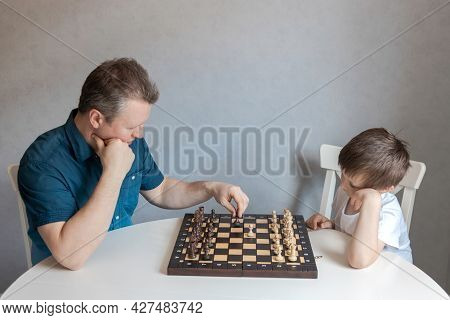 Dad And Son Are Playing A Board Game Of Chess. Time And Games With Children. Logic And Strategy Game