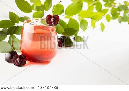 Cold Fresh Fruit Summer Layered Alcohol Cocktail With Cherry Liqueur In Glass With Sliced Fruit, Gre