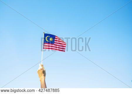 Hand Holding Malaysia Flag On Blue Sky Background. September Malaysia National Day And August Indepe
