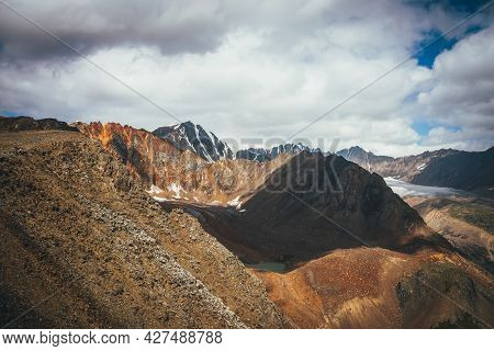 Dramatic Highlands Landscape With Mountain Lake And Glacier Tongue Among Vivid Rocks With Snow. Colo