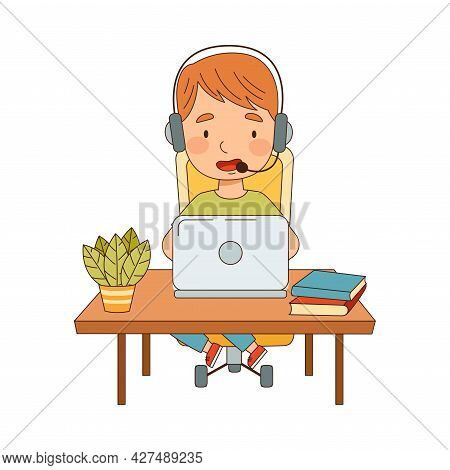 Little Boy At Table With Headphones In Front Of Laptop Training And Doing Homework As Home Study And