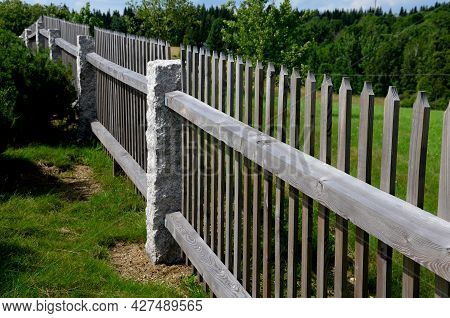 Wooden Fence Made Of Natural Planks. The Columns Are Made Of Roughly Worked Gray Granite. Fencing La