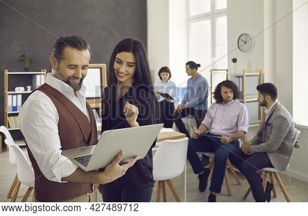 Group Of Businesspeople Working And Communicating Together In Creative Office