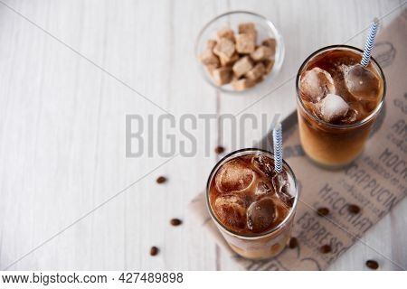 Iced Coffee Latte Cappuccino In A Tall Glass With Cream Or Milk Andbeans, Straws On Light Backgroun