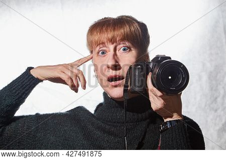 Female Photographer In A Studio In Black Dress With Camera On White Background. Woman Posing Indoors