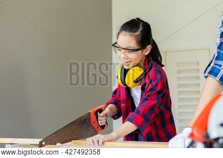 Kid Learning Woodworking In The Craftsman Workshop, Asian Girl Standing With Noise Reduction Earmuff