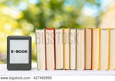 Knowledge. E-book Reader And A Stack Of Books. The Park Is Blurred In The Background. Copy Space. Co