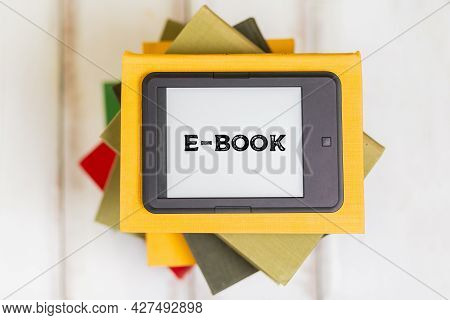 Reading. E-book Reader Is On Top Of A Stack Of Books On A Wooden Background. Flat Lay. Concept Of Ed