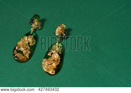 Top View Of Dangle Earrings Made Of Epoxy Resin With Golden Foil Inside Isolated Over Green Backgrou