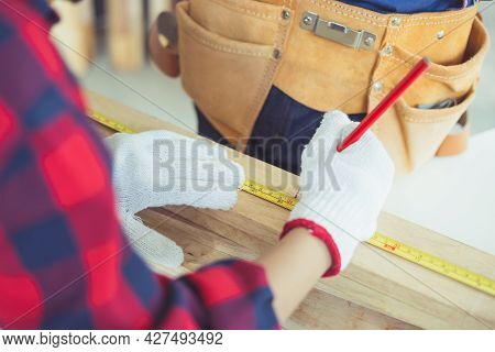 Carpenter Marking Point On Plank, Kid Learning Woodworking In The Craftsman Workshop