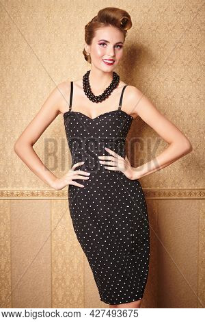 Portrait of a beautiful glamorous woman in elegant evening dress. Pin-up style in clothes, hair and make-up.
