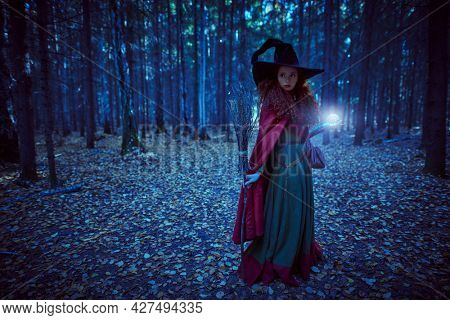 Fabulous young girl witch with magic ball and a broom in a deep forest. Fairy tales. Halloween.
