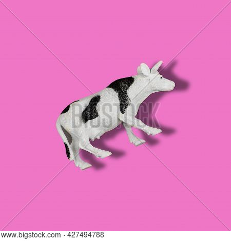 Toy Cow On A Colored Background. Black And White Spotted Plastic Animal Figurine Isolated On Pink Su