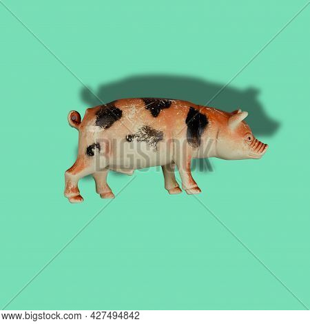 Children's Toy Figurine Of Pig On Colored Background. Old Scratched Toy Isolated Against Green.