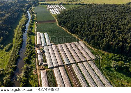 Aerial View Of Agricultural Fields With Greenhouses Between Forest And River