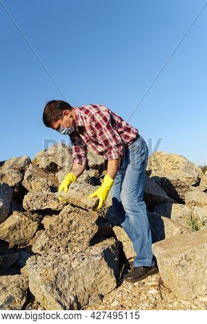 a man works with a pile of stones and broken pieces of concrete, carries construction debris