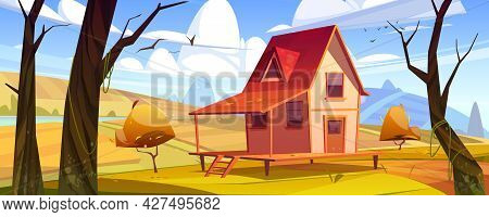 Cottage In Autumn Forest Landscape, Wooden House On Stilts On Yellow Field Among Bare Trees And Dry