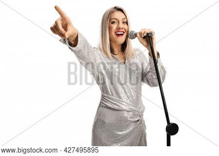 Young female singer with a microphone pointing with finger isolated on white background