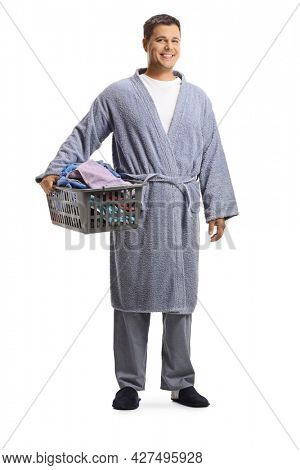 Full length portrait of a young man in a bathrobe holding a laundry basket isolated on white background