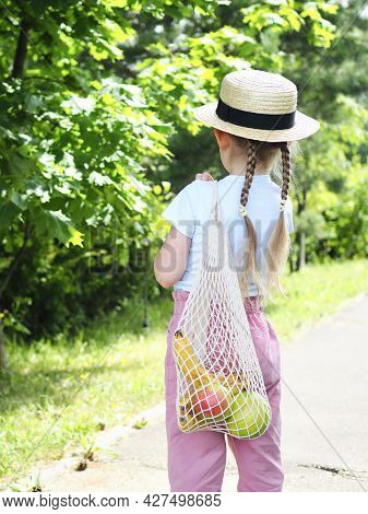 Zero Waste, Plastic Free Concept. Sustainable Lifestyle. Little Girl In Straw Hat Holding Reusable M