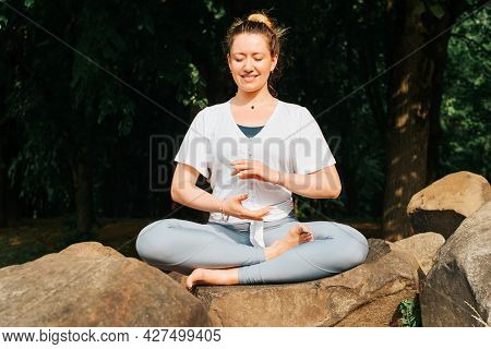 Happy Young Woman Practicing Meditation, Sitting On A Stone In Lotus Position, Yoga Asana In The Mor