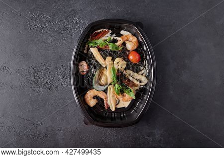 Black Spaghetti Nero With Seafood, Tomatoes And Basil In Black Plastic Container On Dark Background.